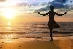 Silueta de la yoga practicante de la mujer durante puesta del sol asombrosa Fotos de archivo libres de regalías