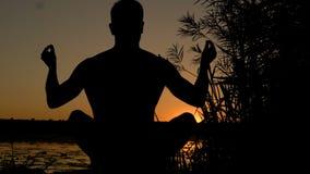 Silueta de la yoga practicante del hombre joven en la playa en la puesta del sol 4K almacen de video