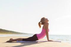 Silueta de la yoga practicante joven de la mujer sana y apta imagenes de archivo