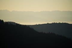 Silueta de las colinas y de las montañas en la puesta del sol Fotografía de archivo