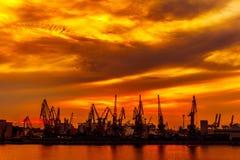 Silueta de las grúas del puerto en un puerto Imágenes de archivo libres de regalías