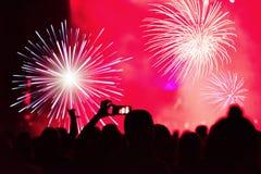 Silueta de las manos que registran los fuegos artificiales del Año Nuevo Fotos de archivo