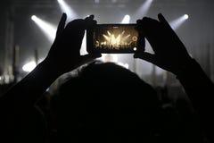 Silueta de las manos que registran los vídeos en el concierto de la música Imágenes de archivo libres de regalías