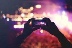 Silueta de las manos que registran los vídeos en el concierto de la música Concierto con las luces, humo del música pop Imagen de archivo libre de regalías