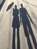 Silueta de las mujeres que detienen un paraguas y a un hombre que se colocan al lado de ella fotografía de archivo libre de regalías