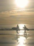 Silueta de las personas que practica surf que caminan en las ondas en la puesta del sol Fotografía de archivo libre de regalías