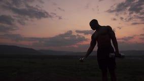 Silueta de las pesas de gimnasia de elevación del culturista muscular afroamericano contra el fondo rosado del cielo de la puesta metrajes