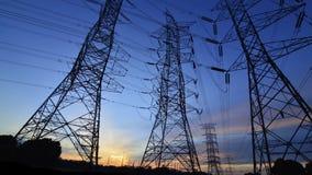 Silueta de las torres de la transmisión de poder más elevado Foto de archivo libre de regalías