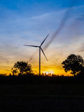 Silueta de las turbinas de viento en la puesta del sol Imagen de archivo