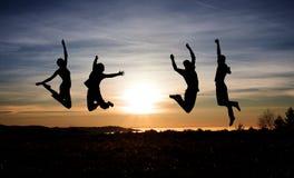 Los adolescentes que saltan en la puesta del sol para la diversión Fotos de archivo libres de regalías