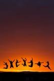 Silueta de los adolescentes que saltan en puesta del sol Fotos de archivo
