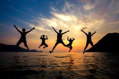 Silueta de los amigos jovenes que se divierten en la playa y el salto Fotografía de archivo libre de regalías