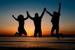 Silueta de los amigos que saltan en la playa Imagenes de archivo
