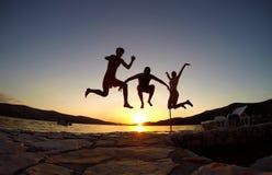 Silueta de los amigos que saltan en la puesta del sol en la playa Fotos de archivo