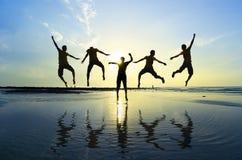 Silueta de los amigos que saltan sobre el sol Imagen de archivo libre de regalías