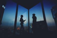 Silueta de los financieros útiles del hombre y de la mujer que se colocan en ventana grande cercana interior del rascacielos de l imagen de archivo