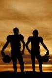 Silueta de los futbolistas que celebran cascos en la puesta del sol Fotografía de archivo libre de regalías