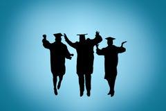 Silueta de los graduados que celebran, saltando Fotos de archivo