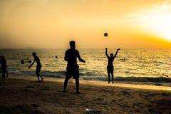 Silueta de los hombres que juegan la bola la playa Fotografía de archivo