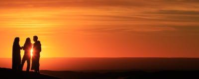 Silueta de los hombres que se colocan en el desierto en la puesta del sol Imagen de archivo