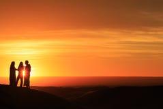 Silueta de los hombres que se colocan en el desierto en la puesta del sol Fotos de archivo libres de regalías