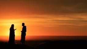 Silueta de los hombres que se colocan en el desierto en la puesta del sol Foto de archivo