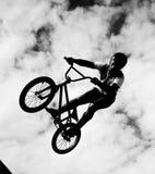 Silueta de los jinetes del bmx en la acción Fotos de archivo