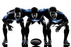 Silueta de los jugadores de los hombres del rugbi Foto de archivo