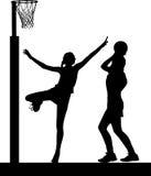 Silueta de los jugadores del netball de las muchachas que saltan y que bloquean Imagen de archivo