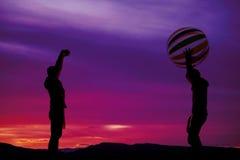 Silueta de los muchachos que lanzan una pelota de playa Imagen de archivo libre de regalías