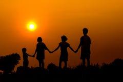 Silueta de los niños que juegan así como puesta del sol Imágenes de archivo libres de regalías