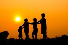 Silueta de los niños que juegan así como puesta del sol Imagenes de archivo