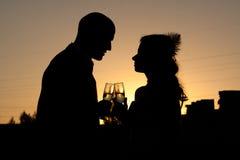 Silueta de los pares de la boda en la puesta del sol Fotos de archivo