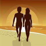 Silueta de los pares felices que caminan a lo largo de la playa en la puesta del sol Fotografía de archivo