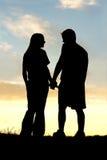 Silueta de los pares felices que llevan a cabo las manos y que hablan en la puesta del sol Fotos de archivo