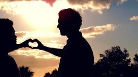 Silueta de los pares homosexuales que hacen el corazón con las manos junto metrajes