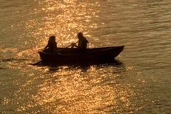 Silueta de los pares de la datación, barco recreativo en el lago en la puesta del sol foto de archivo