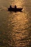Silueta de los pares de la datación, barco recreativo en el lago en la puesta del sol fotos de archivo