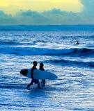 Silueta de los pares de las personas que practica surf Imágenes de archivo libres de regalías