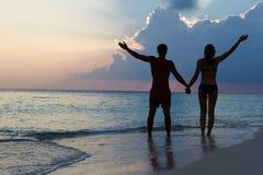 Silueta de los pares que caminan a lo largo de la playa en la puesta del sol Imagen de archivo