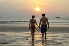 Silueta de los pares que recorren en la playa en las manos de la explotación agrícola de la puesta del sol Tiro horizontalmente e Imagen de archivo libre de regalías