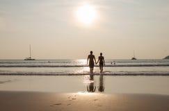 Silueta de los pares que recorren en la playa en las manos de la explotación agrícola de la puesta del sol Tiro horizontalmente e Fotos de archivo
