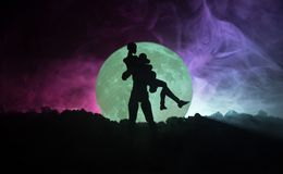 Silueta de los pares que se besan debajo de la Luna Llena Mano de la muchacha del beso del individuo en fondo de la silueta de la Imágenes de archivo libres de regalías