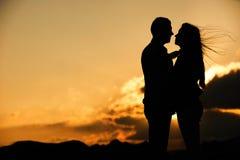 Silueta de los pares que se besan en la puesta del sol Imágenes de archivo libres de regalías