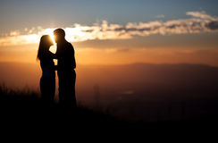 Silueta de los pares que se besan en puesta del sol Imagen de archivo