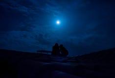 Silueta de los pares que se sientan en un tejado debajo de una Luna Llena fotografía de archivo