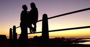 Silueta de los pares romancing cerca de las verjas 4k almacen de video