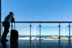 Silueta de los pasajeros que esperan en terraza abierta en aeropuerto Foto de archivo