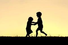 Silueta de los pequeños niños felices que bailan en la puesta del sol