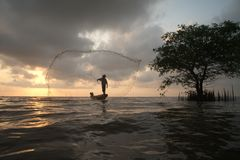 Silueta de los pescadores que lanzan los pescados netos el tiempo de la puesta del sol Fotografía de archivo